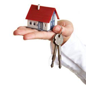 Hand mit kleinem Haus und zwei Schlüsseln