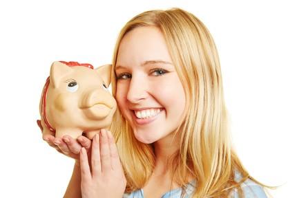 Junge Frau lächelt mit einem großen Sparschwein auf ihrer Hand